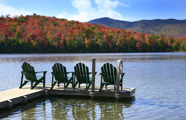 Adirondack chairs on a swim dock, on a peaceful lake in the Adirondack State Park in New York State.
