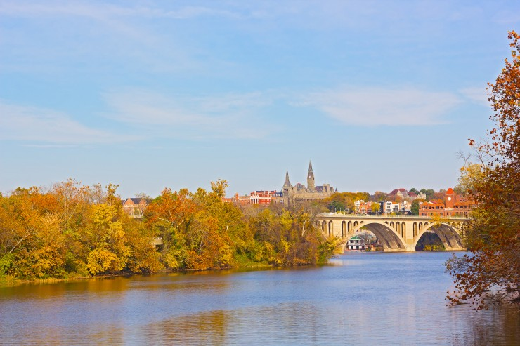 Fall colors of Potomac riverside and Key Bridge, Washington DC. A view on Georgetown University across Potomac River in autumn.