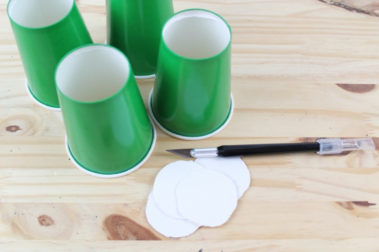Using an exacto knife to cut the bottoms out of the cups.