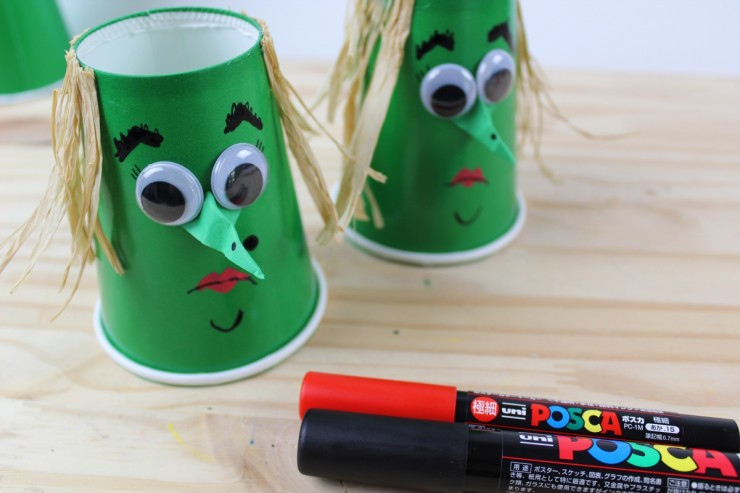 witch face drawn onto the cup using markers.
