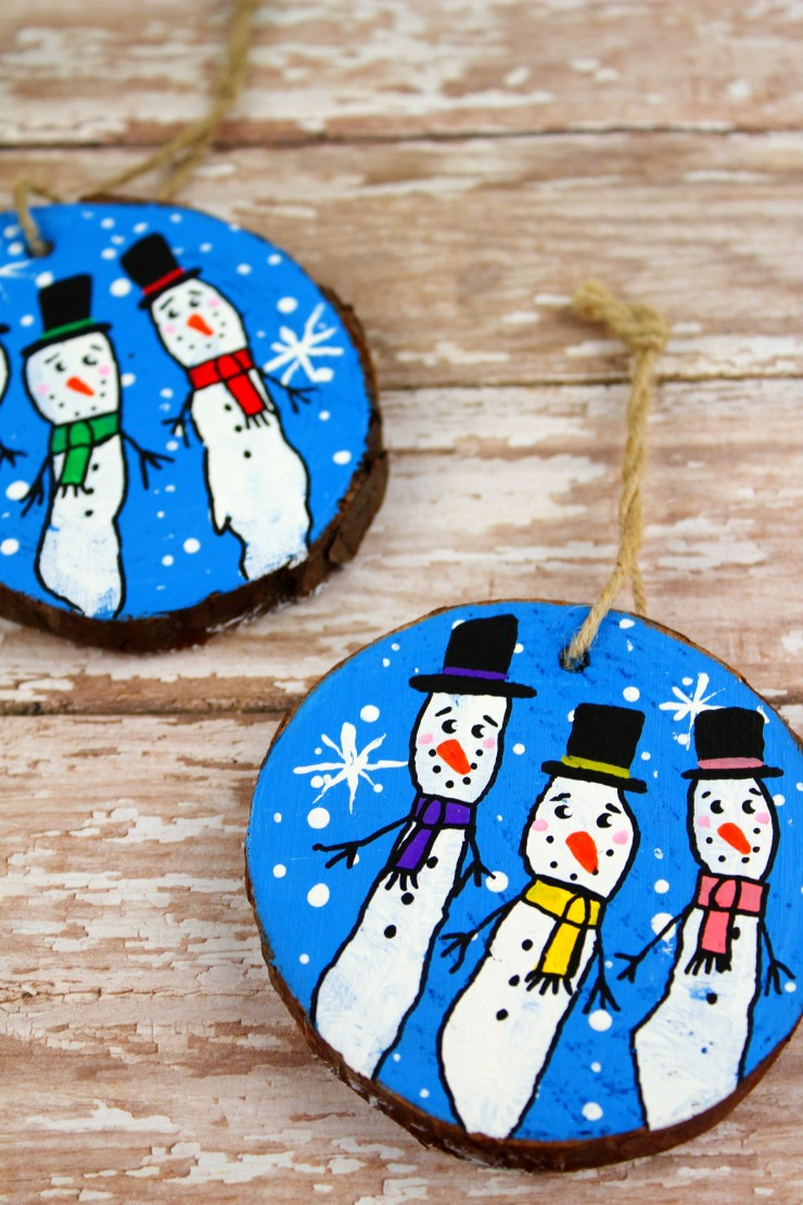 These Wood Slice Fingerprint Snowmen Ornaments are an adorable and festive holiday craft that make for great keepsake gifts that look great on a Christmas tree.  We had so much fun making these Christmas ornaments!