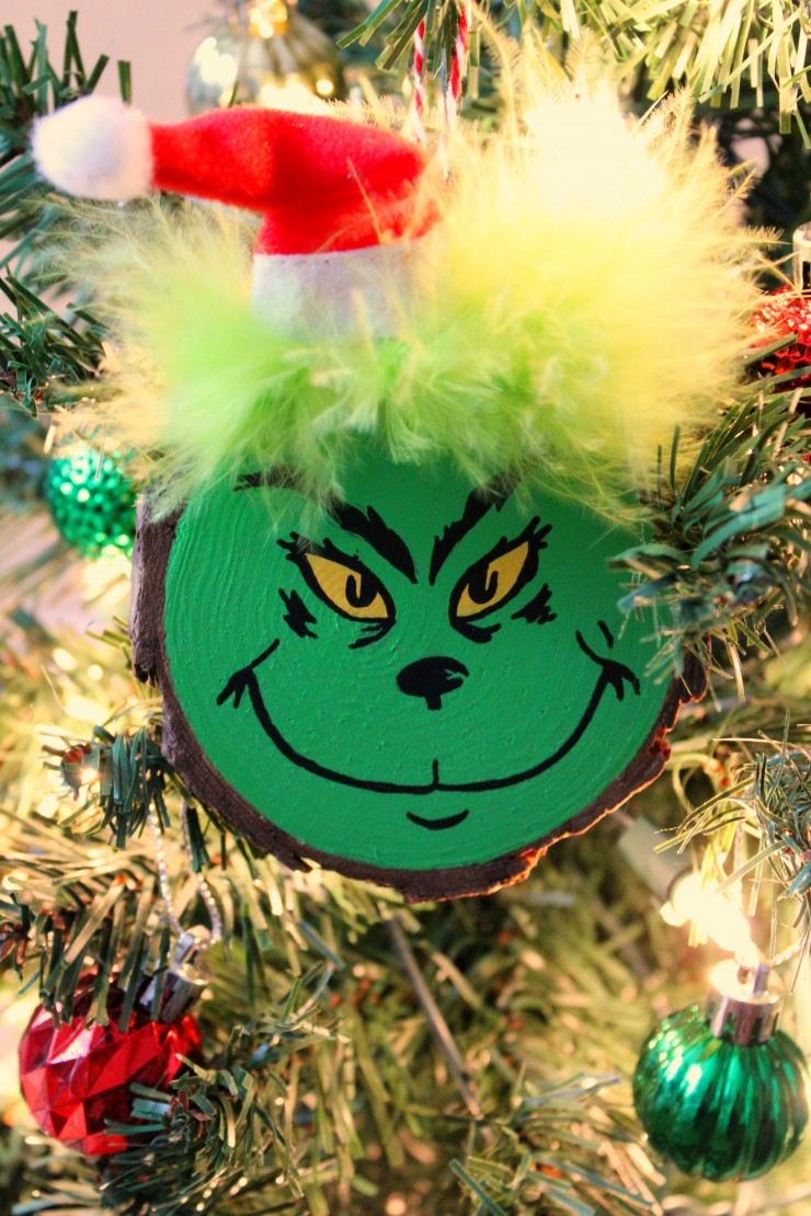 These Wood Slice Grinch Ornaments are a fun and festive holiday craft that make for great gifts and look great on a Christmas tree. We had so much fun making these Grinch inspired Christmas ornaments!