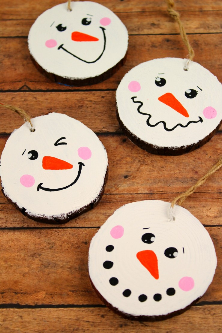 These Wood Slice Snowman Ornaments are an adorable and festive holiday craft that make for great gifts and look great on a Christmas tree.  We had so much fun making these Christmas ornaments!