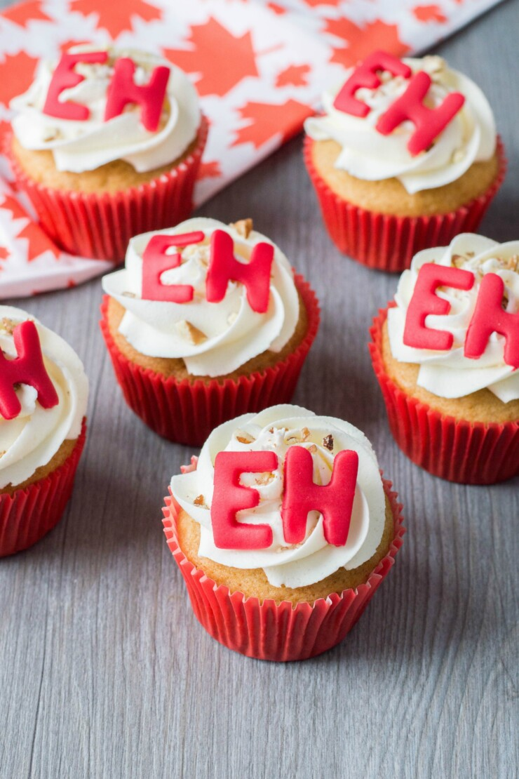 "These Maple cupcakes adorned with fondant ""Eh's"" are the perfect Canada Day weekend treat. Celebrate with family and friends and these adorable Canada Day Cupcakes!"