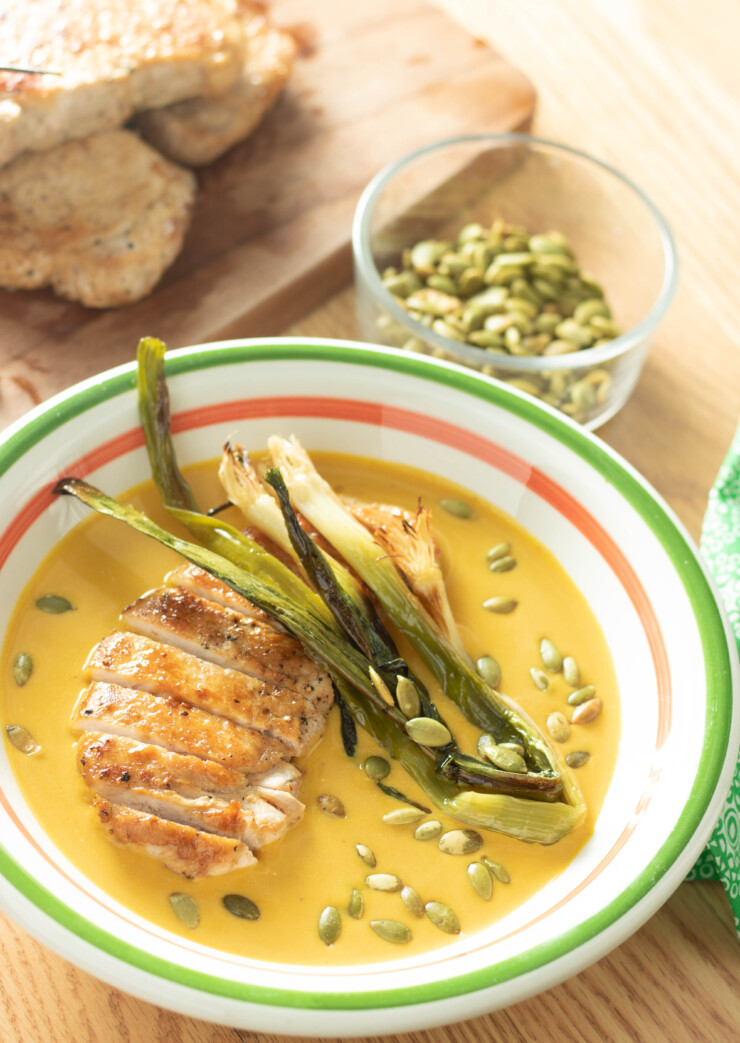 Keep the chill of winter at bay with this hearty Pepita Pork Pumpkin Soup. Creamy pumpkin soup with pan-seared pork loin chops and charred onions, all finished with a sprinkling of toasty pepitas, this soup will warm the body and soul.