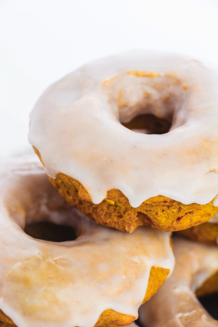 An easy recipe for Baked Pumpkin Donuts that results in soft fluffy and flavourful cake donuts without yeast in just 30 minutes. Coated in a simple vanilla glaze to perfectly complement the pumpkin spice flavours.