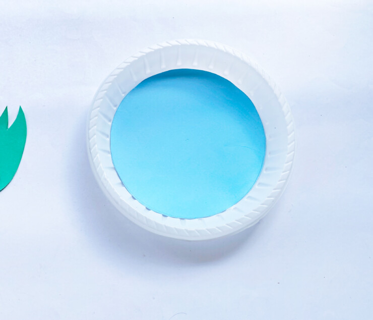 blue paper circle glued onto a paper plate