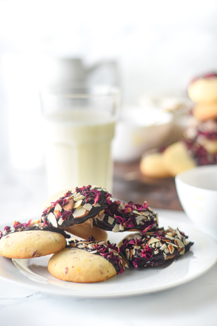 Fragrant Vanilla & Rose Shortbread Cookies are dipped in chocolate and sprinkled with rose petals and almonds in this tasty cookie recipe.