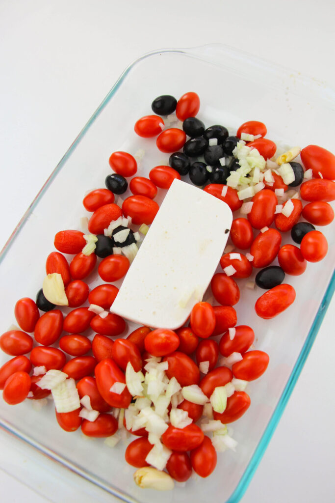 Feta, Cherry Tomatoes, onion, olives and garlic in a casserole dish.