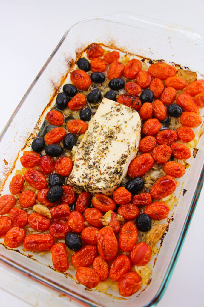Feta, Cherry Tomatoes, onion, olives and garlic in a casserole dish with herbs and olive oil baked.