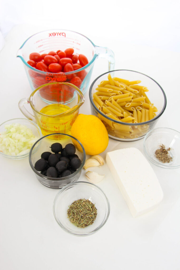 Ingredients for Baked Feta Pasta - Cherry Tomatoes, Pasta, Oil, Lemon, Olives, Herbs, Feta Cheese, Garlic, and onion.