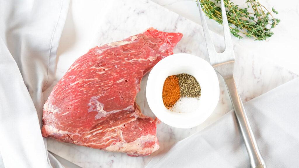 tri tiip steak with seasonings in a bowl