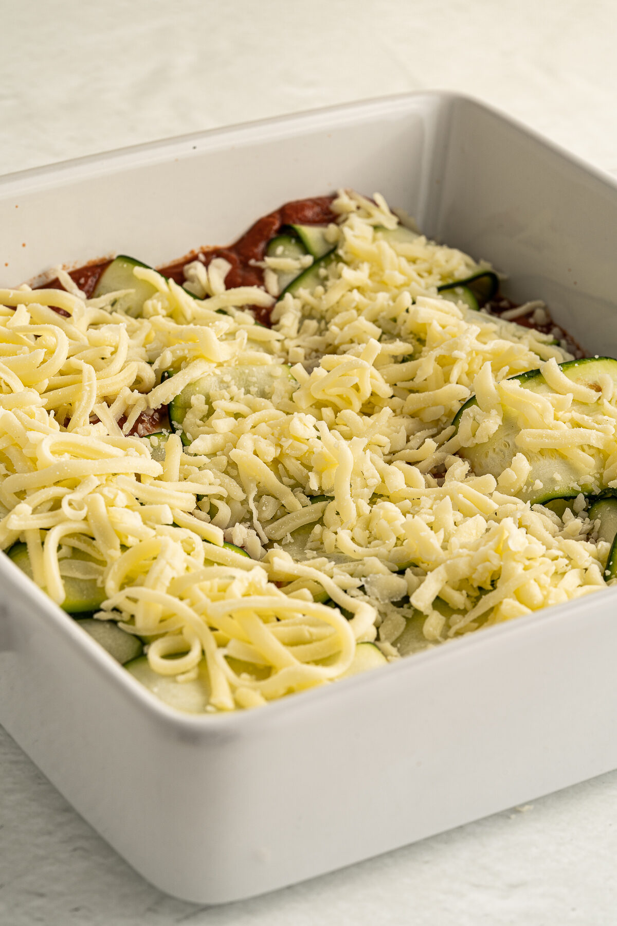 Shredded cheese covering the zucchini bundles