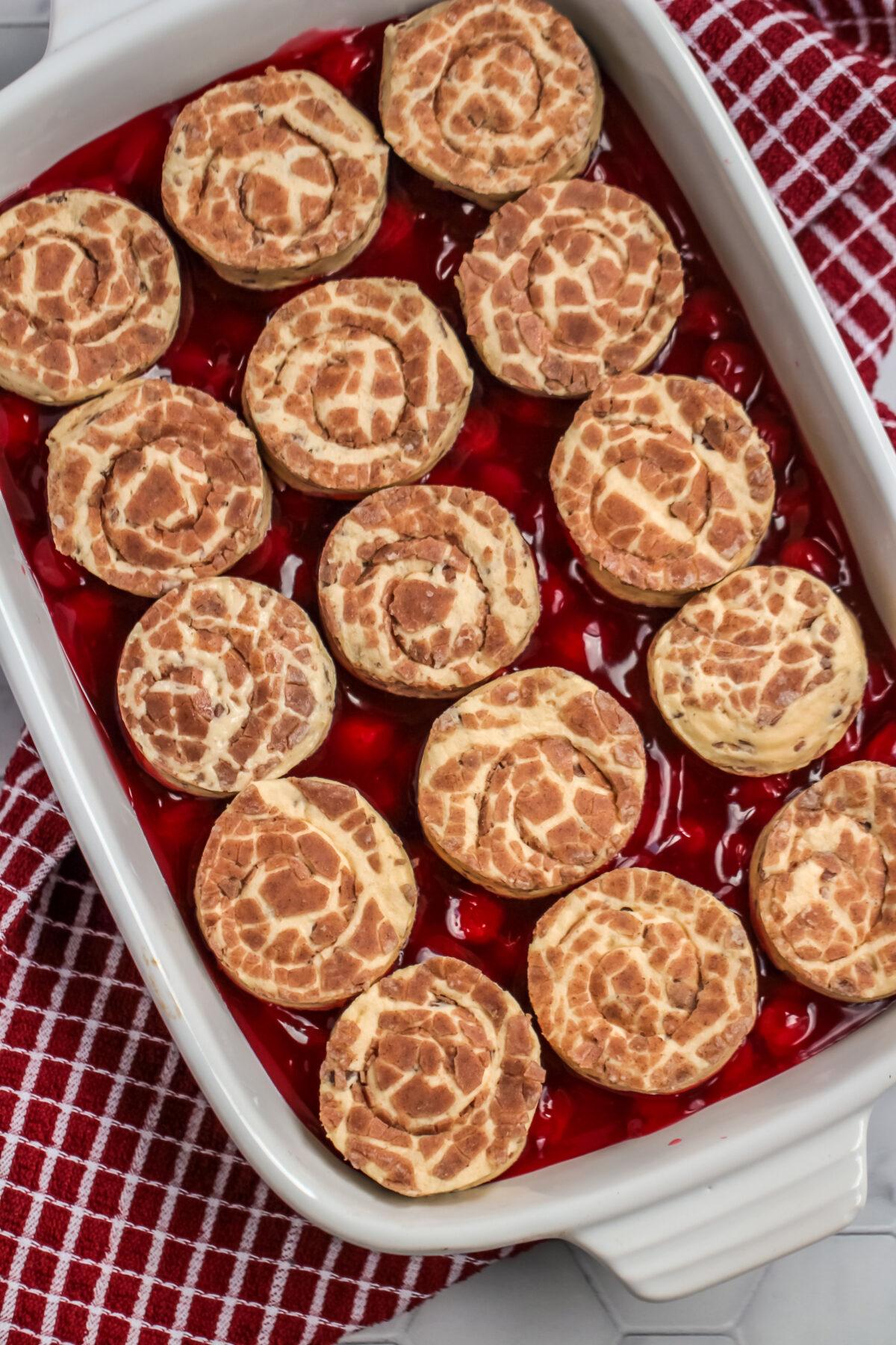 cinnamon rolls on top of cherry pie filling.